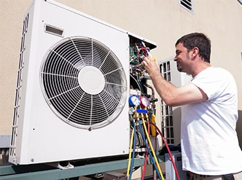 A technician performing A/C maintenance